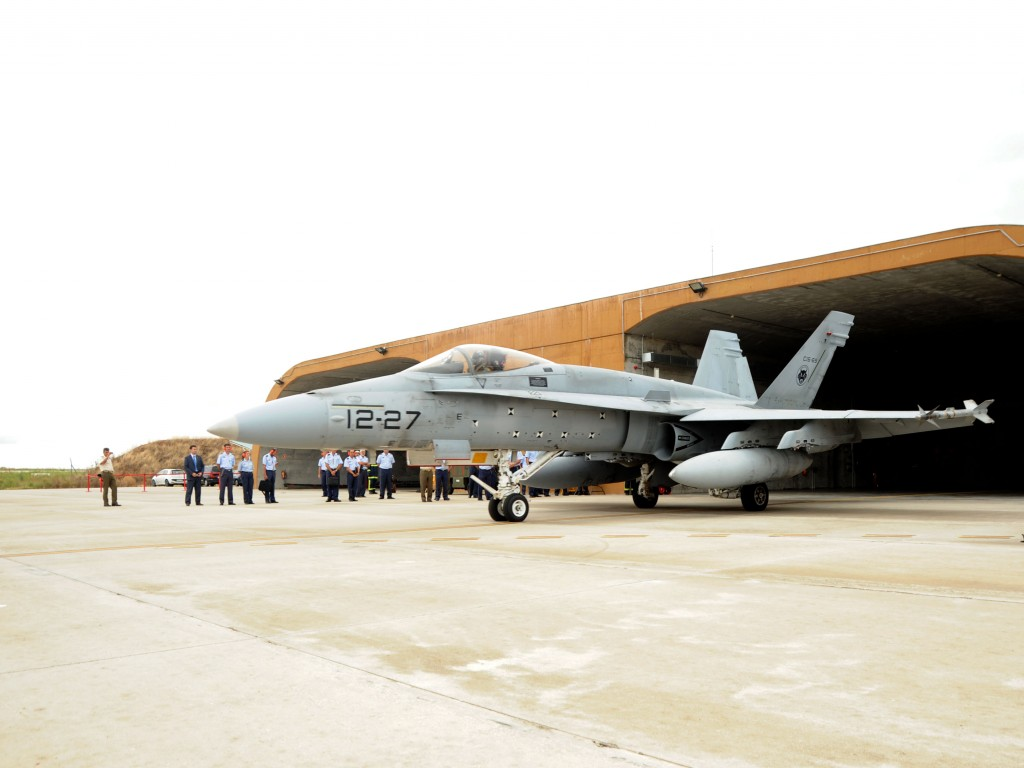 F-18 estacionado frente a un hangar reforzado de alerta.